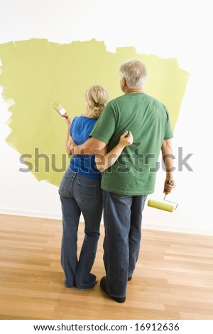 Middle-aged couple painting wall green observing their work. - stock photo