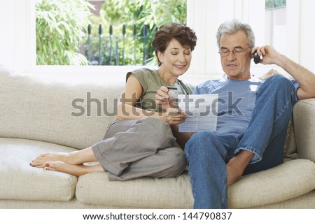 Middle aged couple paying bill by phone on couch at home - stock photo