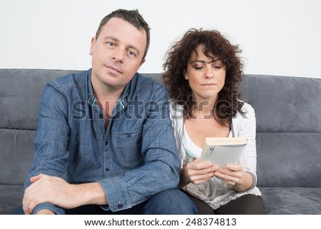 Middle aged couple relaxing in sofa at home reading a book - stock photo