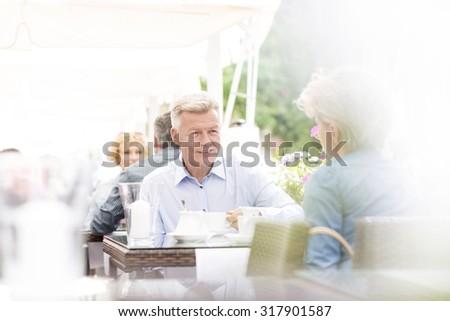 Middle-aged couple sitting at sidewalk cafe on sunny day - stock photo