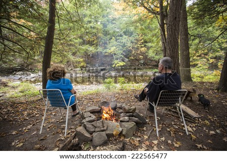 Middle aged couple sitting in front of stream with fire pit in between them & small dog to one side - stock photo