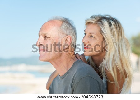 Middle-aged couple sitting in profile gazing out over the ocean on an idyllic hot sunny day at the beach - stock photo