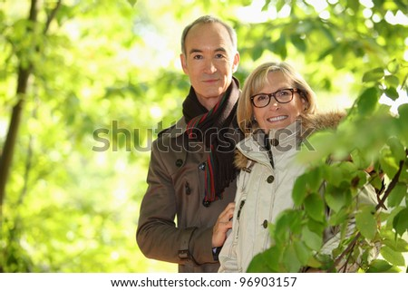 Middle-aged couple walking through park - stock photo