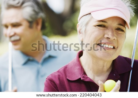 Middle-aged couple with golf clubs - stock photo