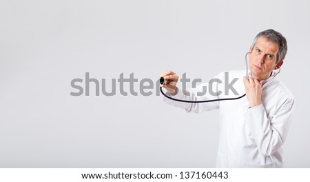 Middle aged doctor listening to empty copy space with stethoscope - stock photo