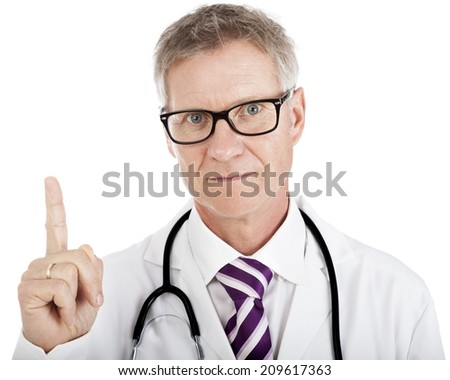Middle-aged doctor pointing above his head towards blank white copyspace while looking at the camera with an intent expression - stock photo