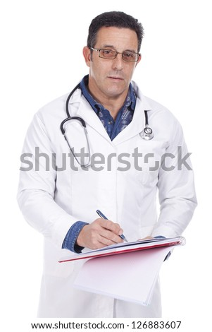 middle aged doctor standing hearing a stethoscope and writing - stock photo