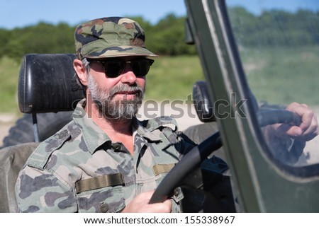 Middle aged driver is driving of a car with an open top. - stock photo