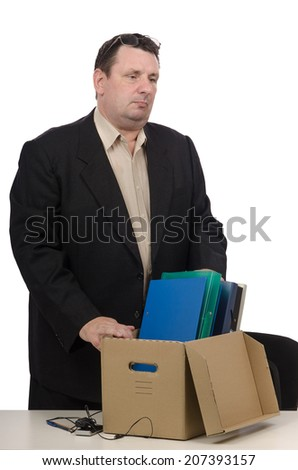Middle-aged employee in black suit has received notification to termination. He packing his belongings on white background - stock photo