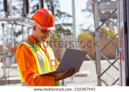 middle aged engineer using laptop in electrical substation - stock photo