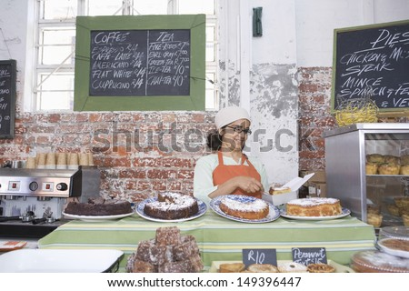 Middle aged female owner working at counter in cake shop - stock photo