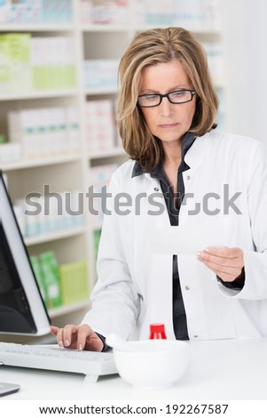 Middle-aged female pharmacist at work standing at the computer on the pharmacy counter checking a prescription with a serious expression - stock photo