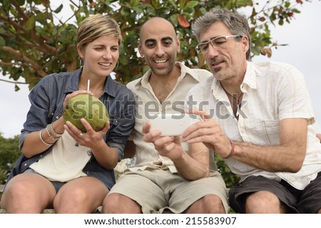 Middle aged group of friends looking at photo on phone - stock photo