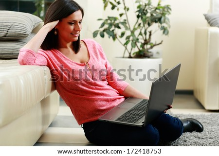 middle-aged happy woman sitting on the floor and using laptop at home - stock photo
