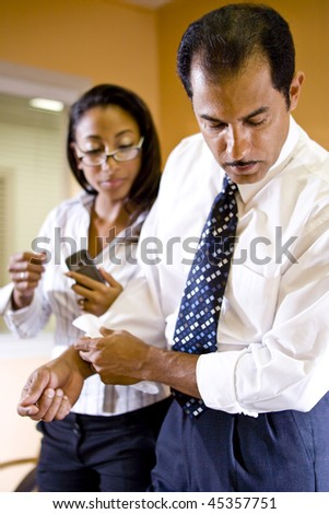 Middle-aged Hispanic businessman and young African-American businesswoman working in office - stock photo
