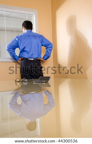 Middle-aged Hispanic businessman in boardroom looking out office window - stock photo