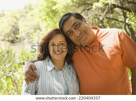 Middle-aged Hispanic couple hugging outdoors - stock photo
