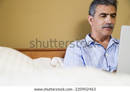 Middle-aged Hispanic man using laptop in bed - stock photo