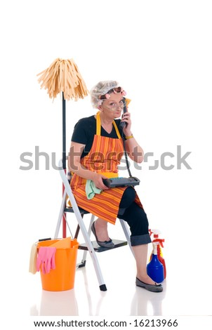 Middle aged housewife, cleaning lady with curlers in hair chatting on phone, gossiping - stock photo