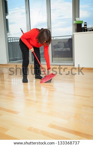 Middle aged housewife dusting wooden floor with red broom - stock photo