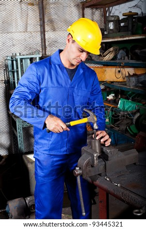 middle aged industrial craftman working in workshop - stock photo