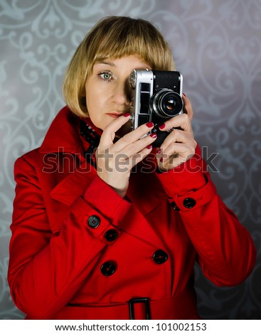 Middle aged lady in red coat taking photos with vintege retro camera - stock photo