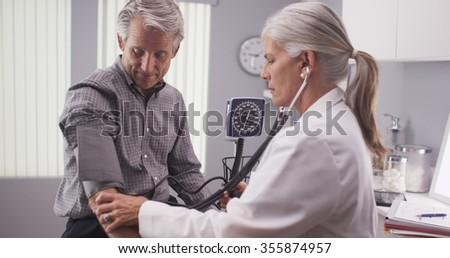 Middle-aged male patient having blood pressure checked - stock photo