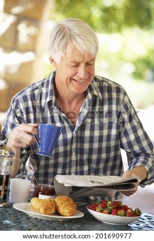 Middle aged man eating breakfast outdoors - stock photo
