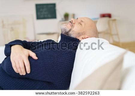 Middle-aged man enjoying a relaxing rest as he dozes on a comfortable sofa at home with his arms folded, profile view - stock photo