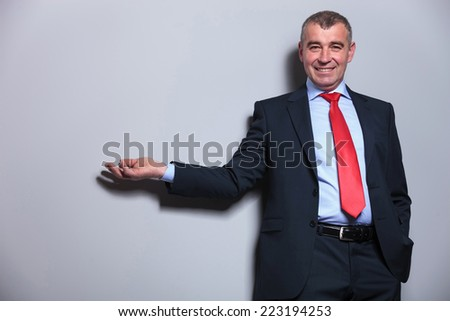 Middle aged man holding his hand in pocket while presenting something on a grey wall. - stock photo