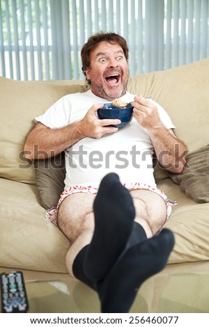 Middle-aged man in his underwea watching TV and eating cereal.  He's laughing at what's on television. - stock photo