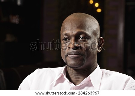 Middle-aged man in pink shirt looking sideways - stock photo