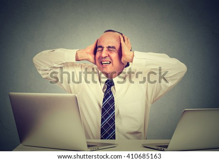 Middle aged man is having stress while using two laptops and working in his office isolated on gray wall background  - stock photo