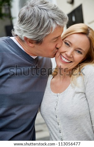 Middle aged man kissing happy woman - stock photo