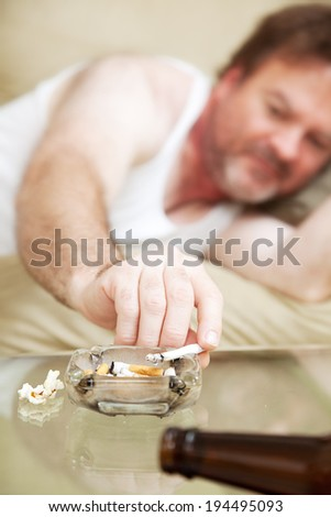 Middle aged man lying on the couch and smoking marijuana.   - stock photo