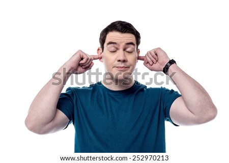 Middle aged man plugging ears with fingers - stock photo