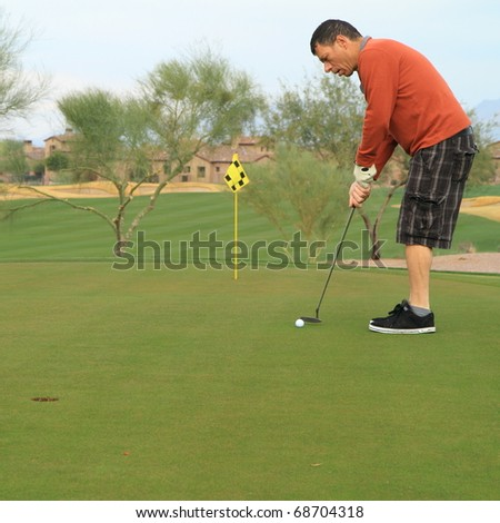 middle-aged man practicing his golf putts - stock photo
