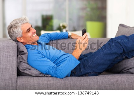 middle aged man reading text message on mobile phone while lying on couch - stock photo