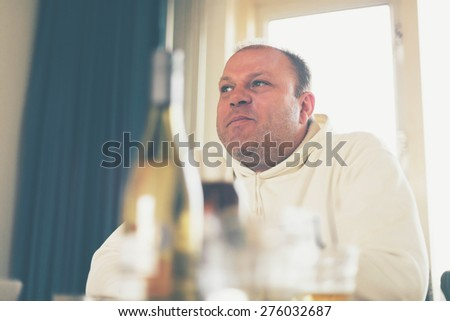Middle-aged man sitting at the dining table indoors thinking looking up into the air with a smile, low angle view - stock photo