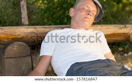 Middle-aged man sitting in the park leaning on a bench feeling a pleasurable sensation after a heroin dose - stock photo