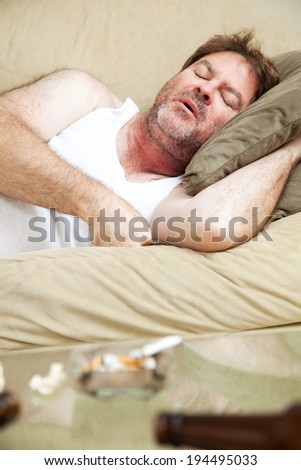 Middle aged man sleeping of a night of drinking and getting high.   - stock photo