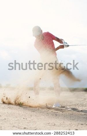 Middle-aged man splashing sand while playing at golf course - stock photo