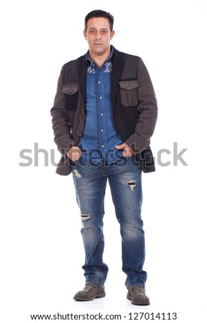 middle aged man standing with his hands on pockets - stock photo