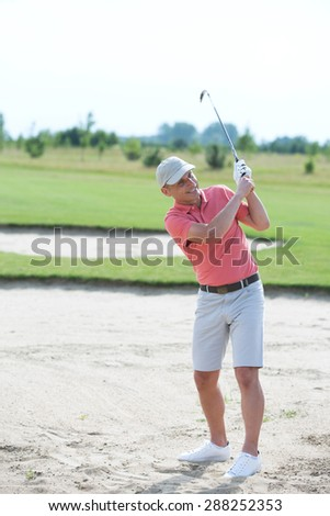 Middle-aged man swinging at golf course - stock photo