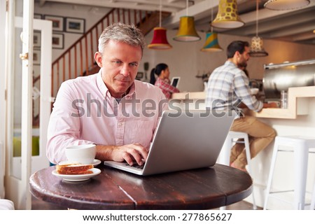 Middle aged man using laptop in a cafe - stock photo