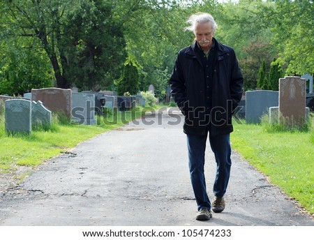 Middle aged man walking in cemetery with head down. - stock photo