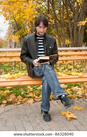 Middle-aged man with a book in autumn park - stock photo