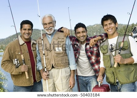 Middle-aged man with three sons holding fishing rods, smiling, (portrait) - stock photo
