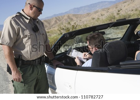 Middle aged man writing on ticket with traffic officer standing by car - stock photo