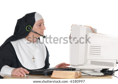 Middle aged nun, sister on computer, connection with god.  Headset with microphone on head - stock photo